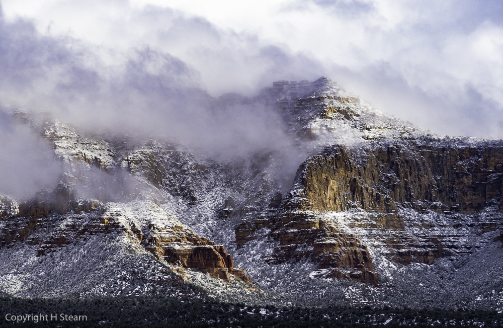 Snow and low clouds blanket red rocks in West Sedona