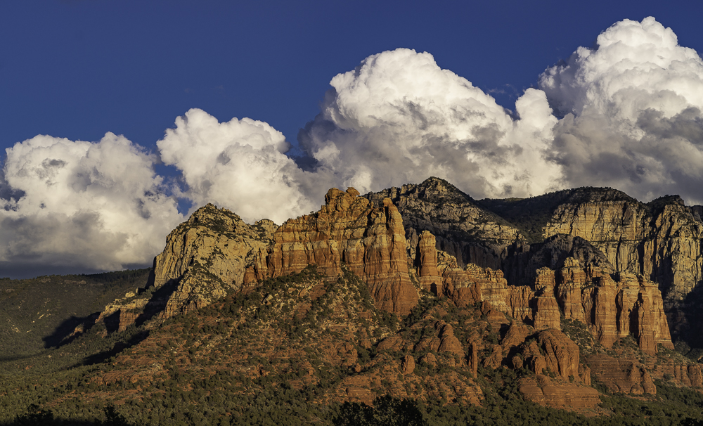 Procession of four identical cumulous clouds over Mogollon Rim