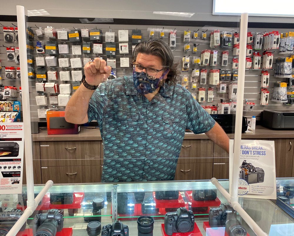 Phil Showing off one of the many plastic shields that are stationed around the store.