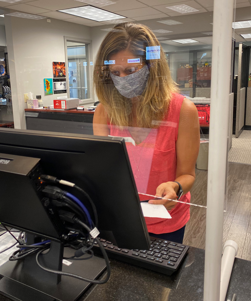 Meredith Reinker, partner at Roberts checks a customer out behind the counter shield