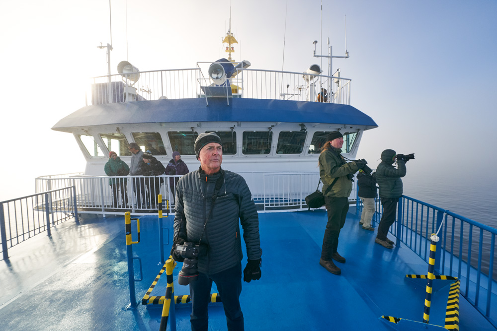 Art Wolfe on the bow of the ship hunting for Fog Bows