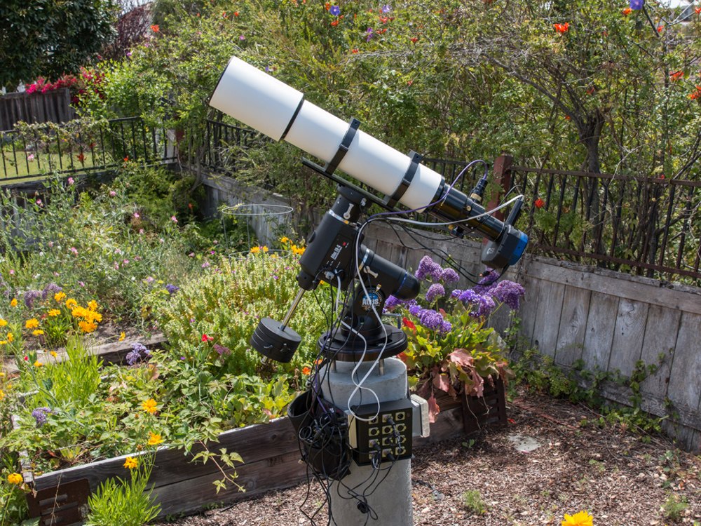 My backyard astrophotography setup with my 130mm refractor telescope, mount and concrete pier. The sketchy fence in the background has since been replaced.
