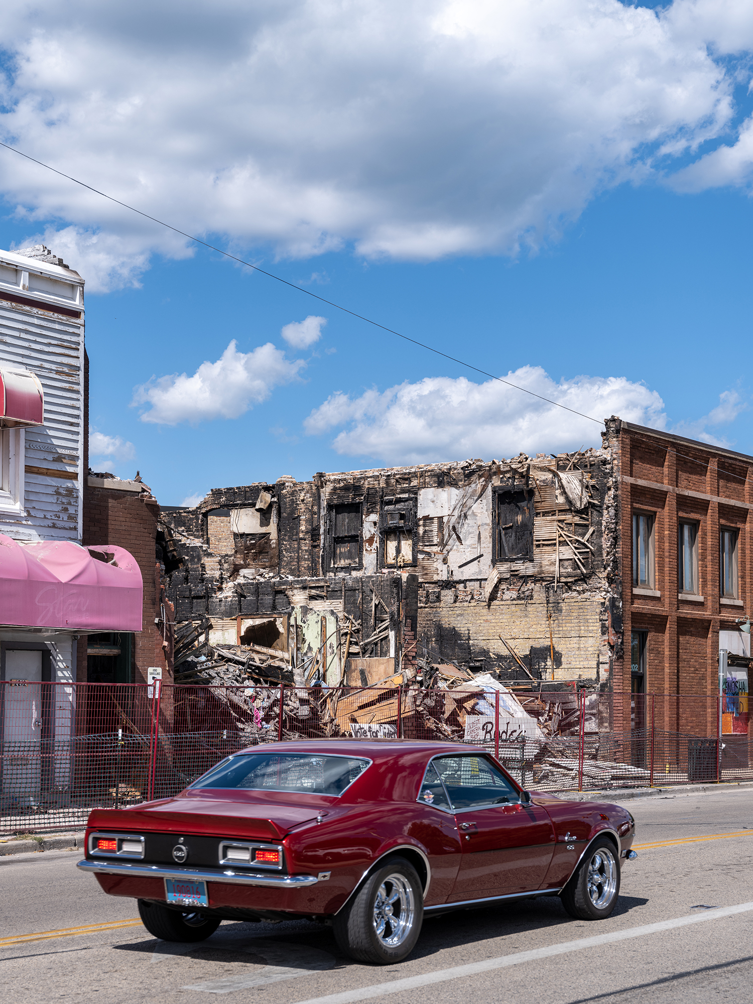 A Car Drives Past a Burned-Out Camera Store