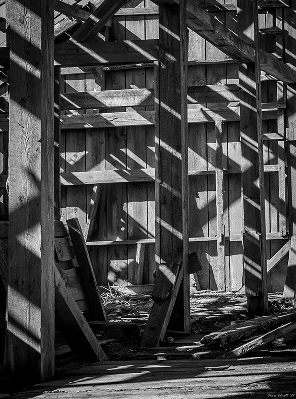 The inside of an old barn, taken at mid-day with sunlight streaming through a decayed roof and interacting with the barn's structural skeleton.